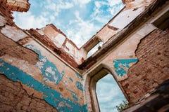 Parte de un edificio de ladrillo abandonado en un fondo de nubes Fotografía de archivo libre de regalías