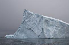 Parte de un iceberg grande en aguas antárticas en un otoño nublado d Imagen de archivo