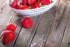 Parte de un plato con la fresa y algunas bayas rojas caidas en ol Imagen de archivo libre de regalías