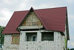 Parte de una casa inacabada del ladrillo gris con un ático y un tejado debajo de las tejas rojas imagenes de archivo
