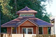 Parte de una casa de madera marrón con las ventanas debajo de un tejado tejado contra la perspectiva de árboles verdes fotos de archivo