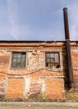 Parte de una fábrica vieja del ladrillo rojo con una chimenea oxidada vieja fotografía de archivo libre de regalías