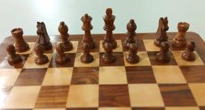 Parte de xadrez de madeira na placa de xadrez pronta para jogar imagens de stock royalty free