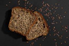 Parte del cierre multi sano marrón del pan del grano para arriba en fondo negro foto de archivo