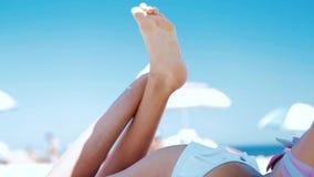 Parte del cuerpo trasera de la mujer atlética hermosa que broncea en bikini en la playa arenosa en el verano El modelo con el cue almacen de video
