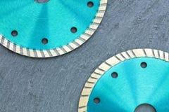 Parte del diamante que corta las ruedas del color esmeralda contra la perspectiva del granito gris fotografía de archivo libre de regalías