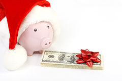 Parte del porcellino salvadanaio con il cappello di Santa Claus e pila di banconote in dollari dell'americano cento dei soldi con Fotografia Stock