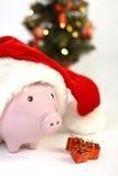 Parte del porcellino salvadanaio con il cappello di Santa Claus e tre piccoli alberi di Natale brillanti e del regalo che stanno  Fotografie Stock Libere da Diritti