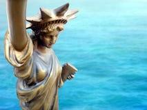 Parte del primo piano della statua della libertà metallica bronzea dorata con il fondo blu della superficie del mare Immagine Stock