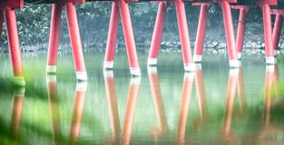 Particolare del ponte rosso di legno con il fondo dell'acqua. Fotografie Stock
