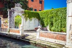 Parte del terraplén con el arco viejo entrelazado con las plantas verdes en el canal en Venecia, Italia foto de archivo