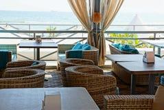 Parte del terrazzo del ristorante con le tavole e le sedie sui precedenti del mare immagini stock libere da diritti