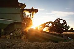 Parte delantera de una cosechadora en la puesta del sol Imagen de archivo