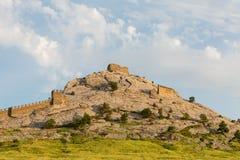 Parte dell'alta montagna di Sudak della fortificazione di vecchia fortezza contro i precedenti del cielo blu Fotografia Stock Libera da Diritti
