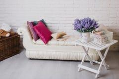 Parte dell'interno con lo strato ed i cuscini decorativi, tavola di legno bianca con i libri su  Fotografia Stock Libera da Diritti