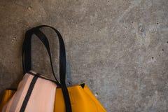 Parte della borsa femminile di cuoio gialla sul backgroud grigio della parete immagine stock