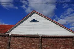 Parte della casa con una soffitta bianca con una piccola finestra sotto un tetto piastrellato rosso dietro un recinto marrone di  fotografie stock