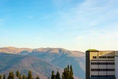 Parte della costruzione della località di soggiorno sulla collina Picchi di montagne veduti in fotografia stock