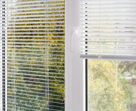 Parte della finestra di plastica moderna con le veneziane bianche Fotografia Stock