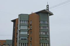 Parte di alta casa marrone grigia con le finestre ed i balconi sul cielo Immagini Stock Libere da Diritti
