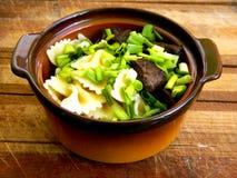 Parte di fegato fritto del manzo nei grandi pezzi con pasta sotto forma di arco con le cipolle verdi tagliate in un vaso di argil immagini stock libere da diritti