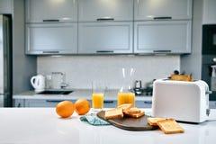 Parte di pani tostati su un bordo di legno con succo d'arancia La prima colazione è servita su una tavola con il tovagliolo blu-c immagine stock libera da diritti