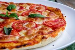 Parte di pizza con formaggio sul piatto bianco Primo piano Fotografia Stock