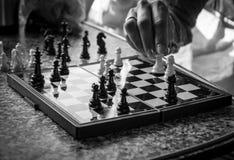 Parte di scacchi commovente della mano Immagini Stock