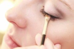 Parte di trucco femminile dell'occhio del fronte che si applica con la spazzola Fotografia Stock Libera da Diritti