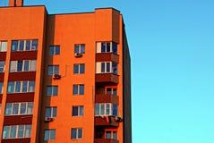 Parte di un grattacielo marrone con i balconi e le finestre su un fondo blu Fotografie Stock Libere da Diritti