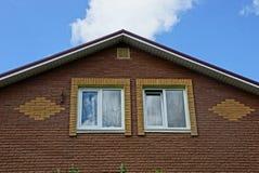 Parte di un sottotetto marrone dei mattoni con le finestre su un fondo del cielo Fotografie Stock