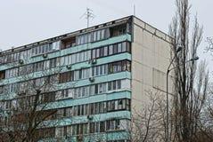 Parte di una casa alta con i balconi e le finestre su un fondo degli alberi e del cielo Fotografia Stock Libera da Diritti