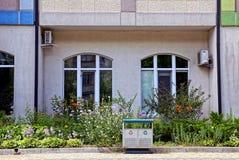 Parte di una costruzione con le finestre dietro un letto di fiore con le piante e un bidone della spazzatura Immagini Stock