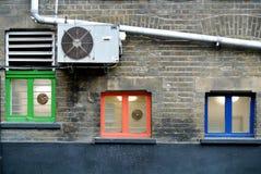 Parte di una facciata della costruzione con le piccole finestre colorate fotografia stock libera da diritti