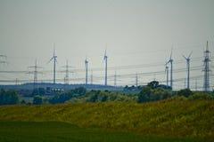 Parte di una linea elettrica con i generatori eolici in Baviera, Germania fotografia stock