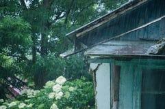 Parte di vecchia casa nel villaggio Intorno agli alberi Sta versando la pioggia fotografia stock libera da diritti