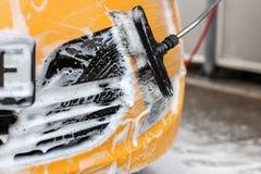 Parte dianteira amarela do carro lavada no carwash do saque do auto, FOA branca do champô imagem de stock