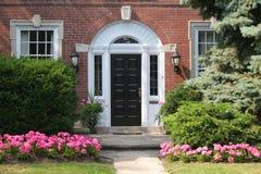 Parte dianteira da casa com flores Fotos de Stock Royalty Free