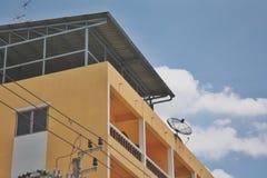 A parte dianteira da construção ou do apartamento alaranjado ou residência com um fundo do céu e umas nuvens brancas fotografia de stock