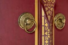 Parte dianteira da porta de madeira vermelha bonita ao fundo do estilo de Butão com o botão de porta do metal do ouro imagem de stock royalty free