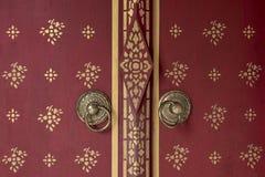 Parte dianteira da porta de madeira vermelha bonita ao fundo do estilo de Butão com o botão de porta do metal do ouro fotografia de stock royalty free