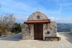 Parte dianteira de uma capela ortodoxo de pedra pequena entre as montanhas imagens de stock