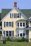 Parte dianteira de uma casa amarela e de um céu azul Imagens de Stock Royalty Free