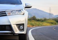 Parte dianteira do estacionamento de prata novo do carro na estrada asfaltada Imagem de Stock