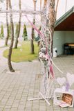 Parte do arco do casamento decorado com flores e fitas perto das caixas de madeira com corações Imagem de Stock