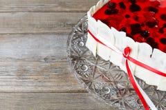 Parte do bolo da baga com a geleia vermelha amarrada com as fitas no fundo de madeira Fotos de Stock Royalty Free