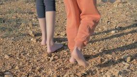 Parte do corpo dos pés das crianças refugiados pequenos que estão em uma estrada de terra com os pés descalços sem sapatas no fim filme