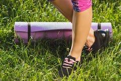 Parte do corpo: mulher na roupa e nas sapatilhas do esporte com uma esteira Fotos de Stock Royalty Free