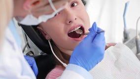 Parte do dentista que usa o espelho dental durante a verificação acima filme