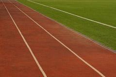 Parte do estádio verde dos esportes e das pistas marrons Foto de Stock